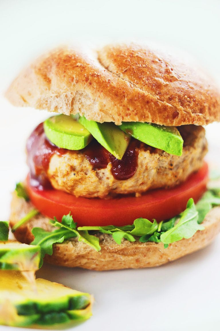 Turkey burger in between a bun with tomatoes, greens, and avocado slices.