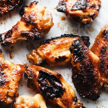 Sriracha honey chicken wings on white parchment paper.