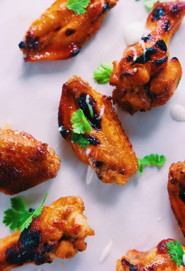 sriracha honey chicken wings on parchment paper