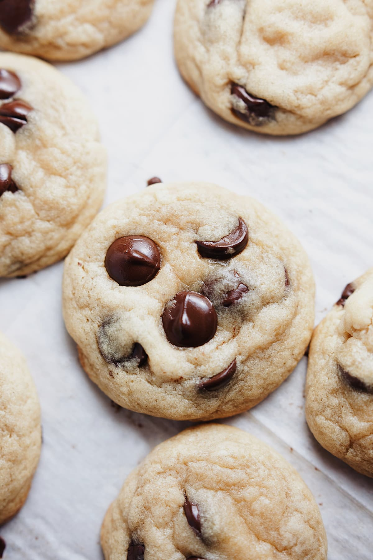 Chewy chocolate chip cookies laid out on parchment paper.