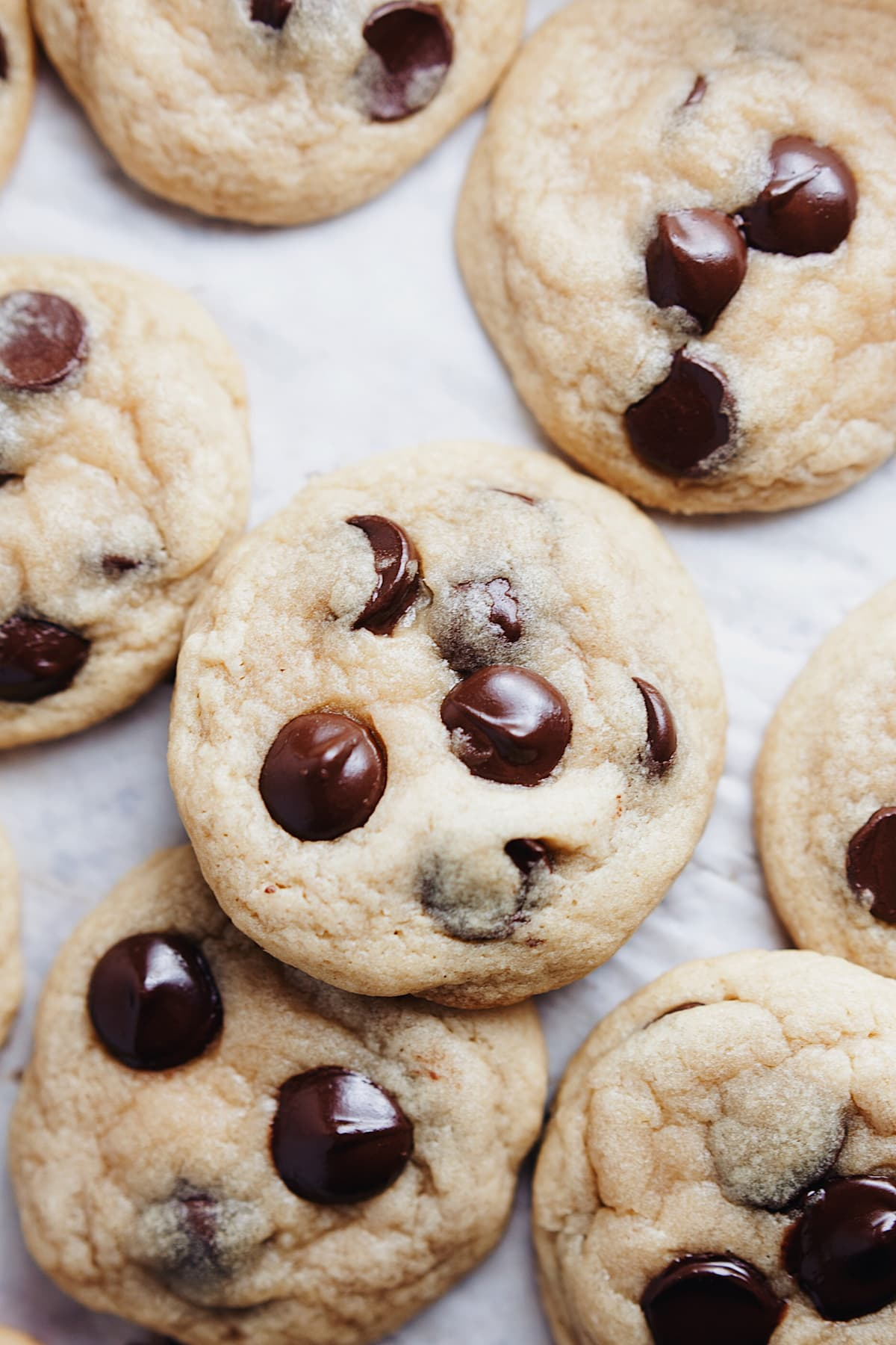 Chewy Ghirardelli chocolate chip cookies laid out on parchment paper.