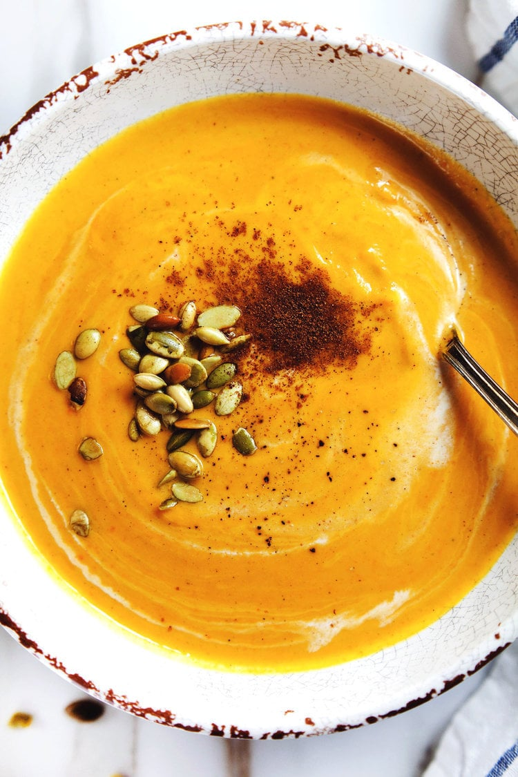 A bowl of panera autumn squash soup in a white bowl with a spoon in it.
