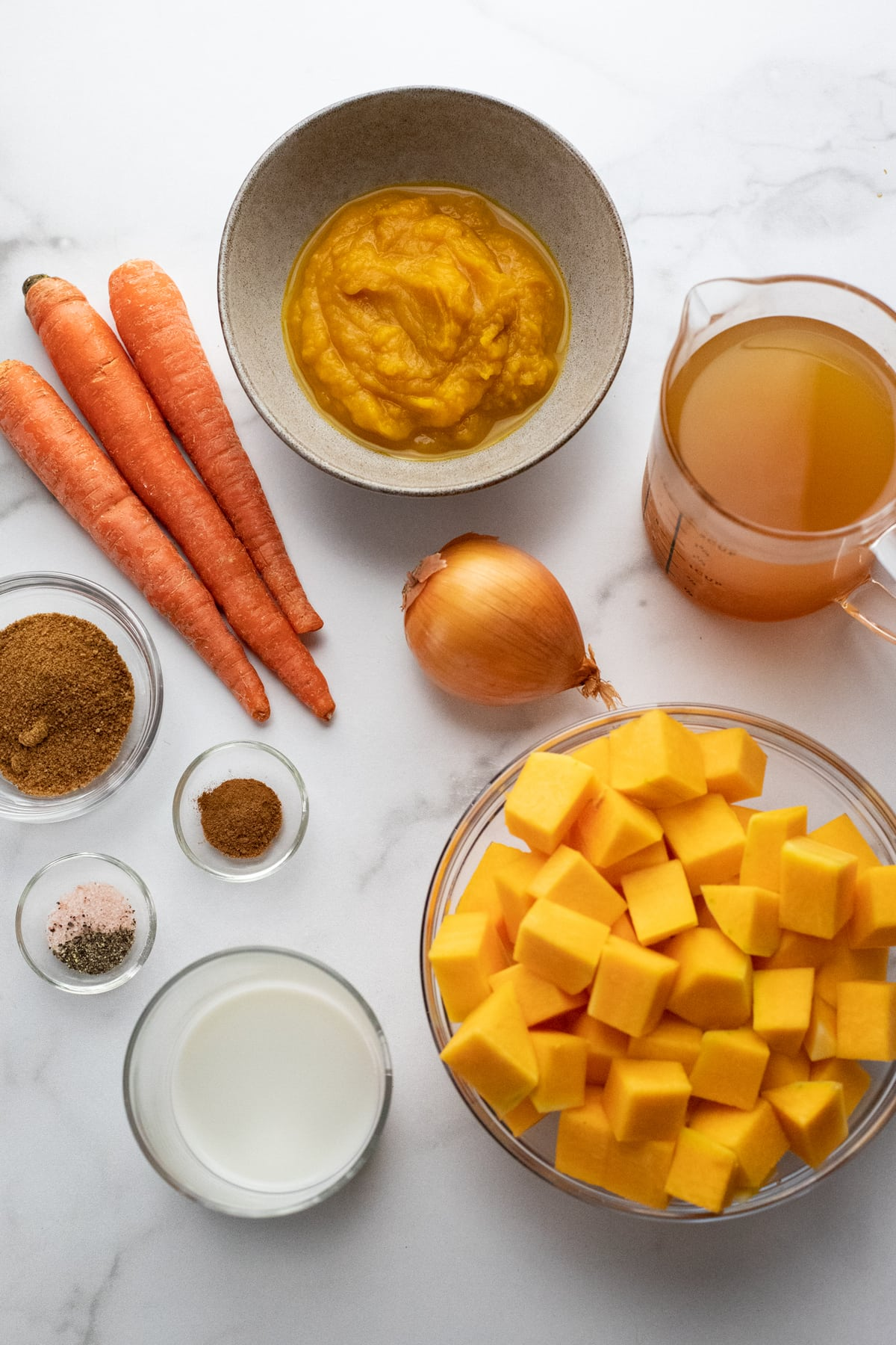 Ingredients for butternut squash soup arranged on white counter.