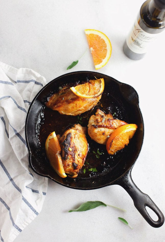 A black skillet pan with citrus chicken with orange slices on a white background