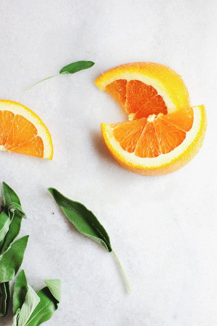 Orange slices with sage leaves on a white background