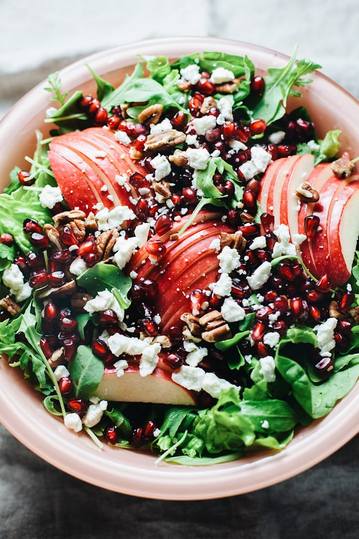 A close up of a bowl of apple slices, pomegranate seeds on a bed of greens.