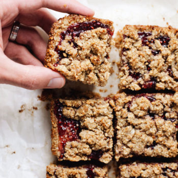 raspberry oatmeal bars on parchment paper with a hand picking a bar up