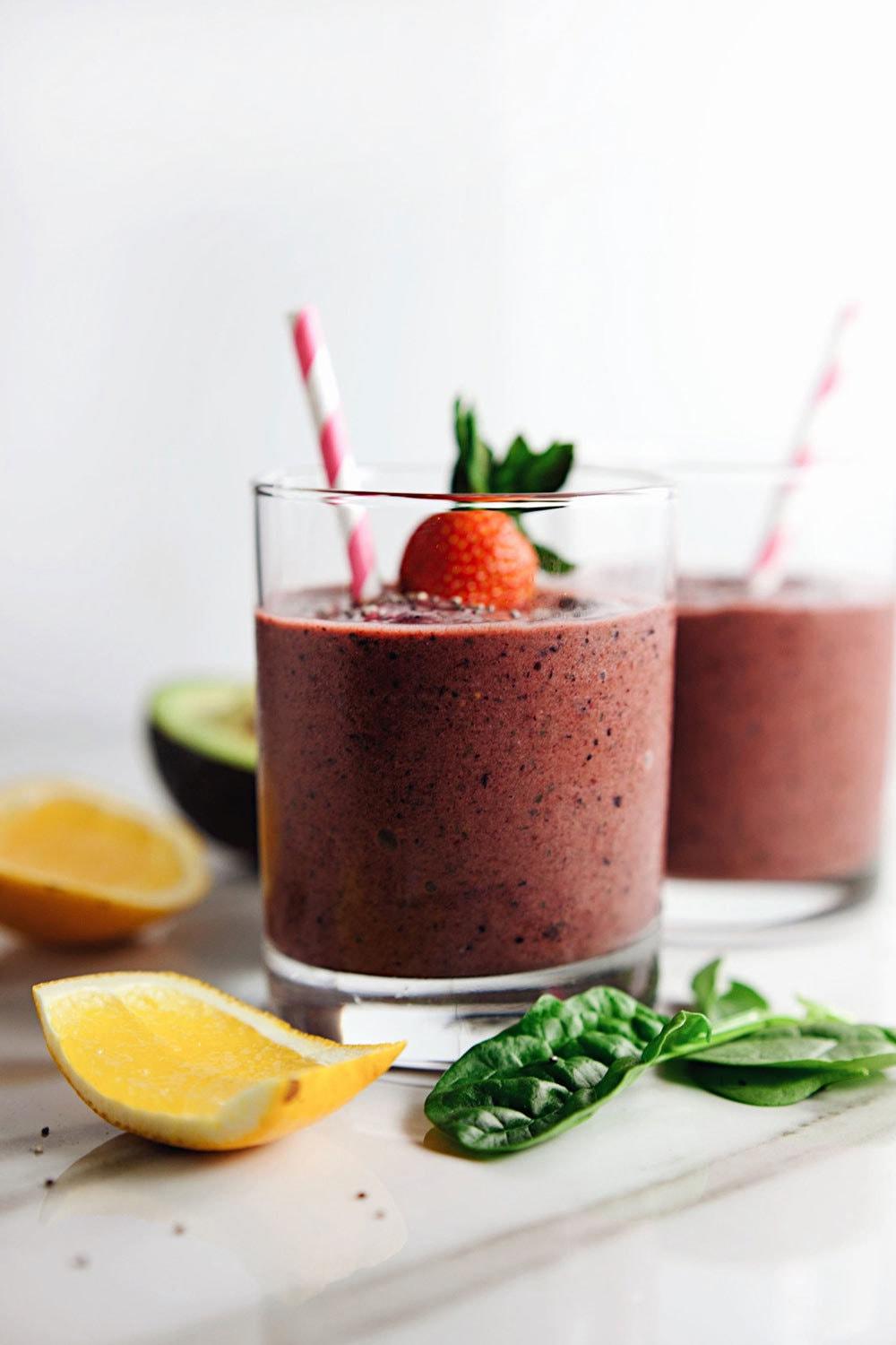 clear glasses filled with purple berry smoothie with pink striped straws in them on white counter with vegetables and fruit arranged around glasses.