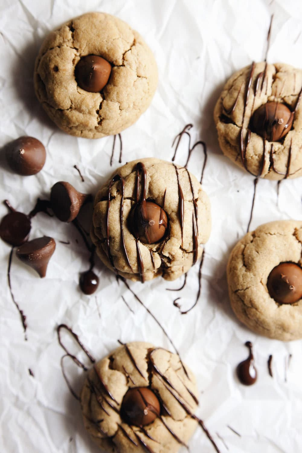 Peanut butter blossom cookies drizzled with melted chocolate on white parchment paper.