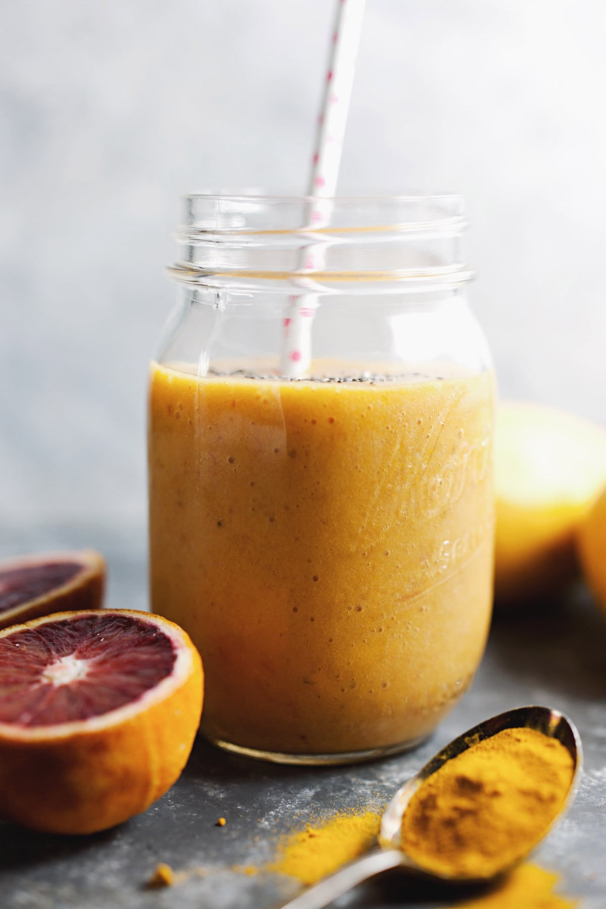 A mason jar with orange smoothie and a straw in it with blood oranges in bottom corner.