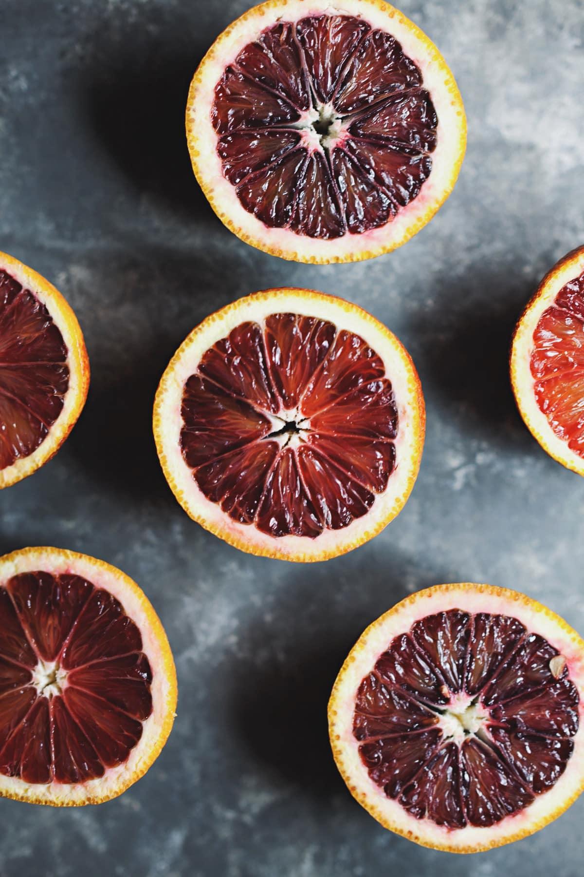 blood oranges cut in half on gray background.