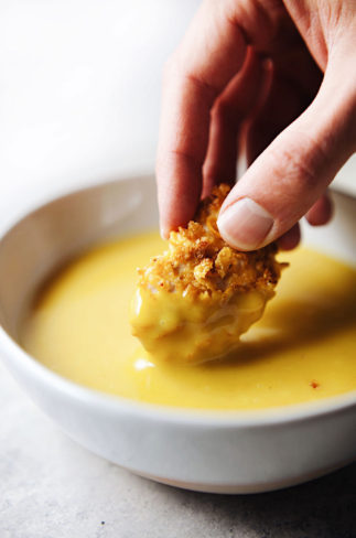 Hand dipping chicken nugget into white bowl of yellow sauce.
