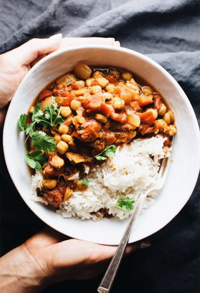 hand holding bowl of moroccan stew and rice.