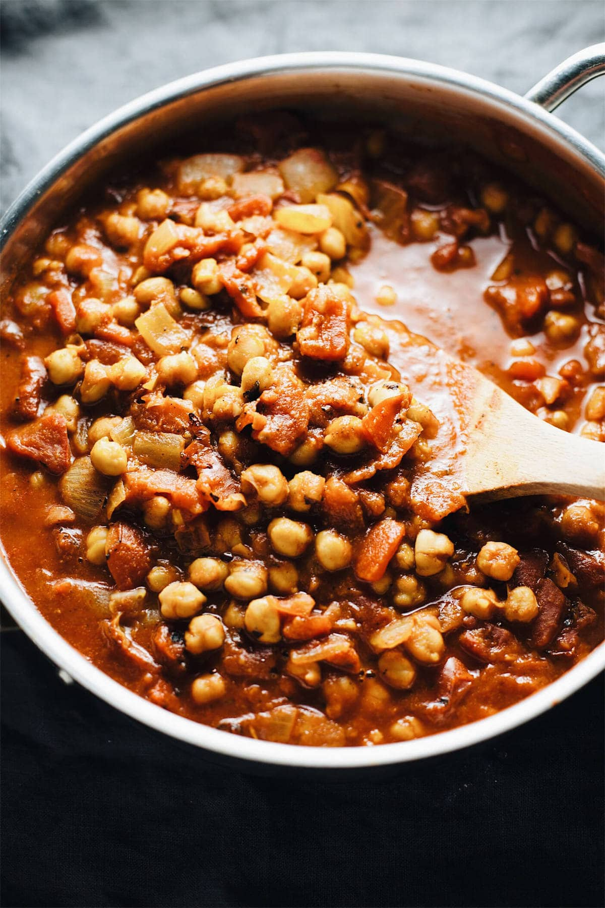 a pan of moroccan chickpea stew with a wooden spoon in it.