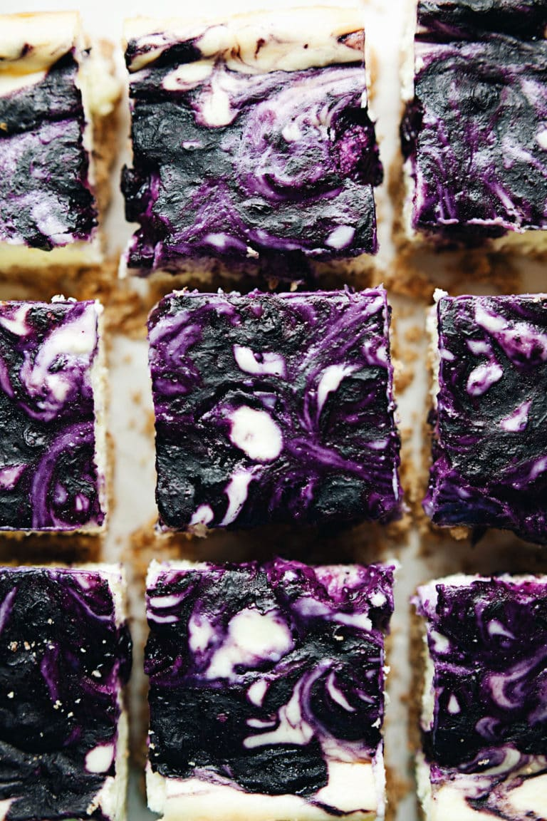 Creamy blueberry cheesecake bars with an almond graham cracker crust! SO decadent and beautiful. | asimplepalate.com #cheesecake #dessert #blueberrydessert #bars
