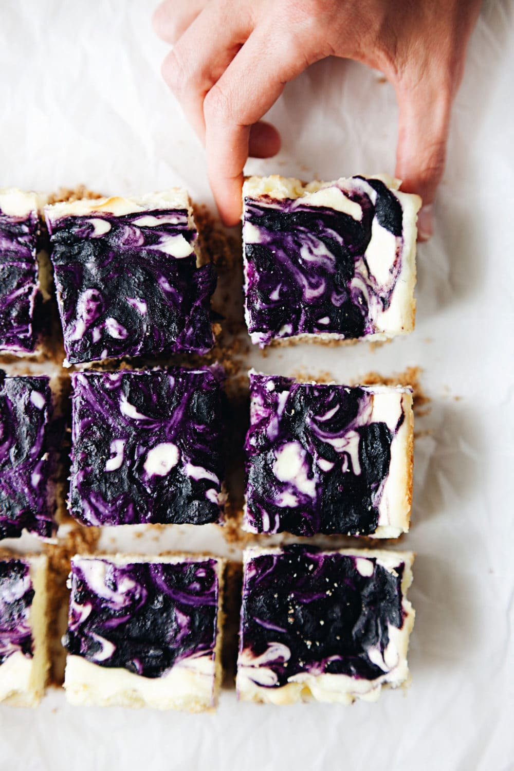 Creamy blueberry cheesecake bars with an almond graham cracker crust! SO decadent and beautiful. | asimplepalate.com #cheesecake #dessert #blueberry #bars