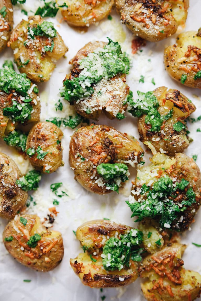 Garlic-y, smashed potatoes with parmesan cheese and refreshing pesto flavor! YUM. | asimplepalate.com