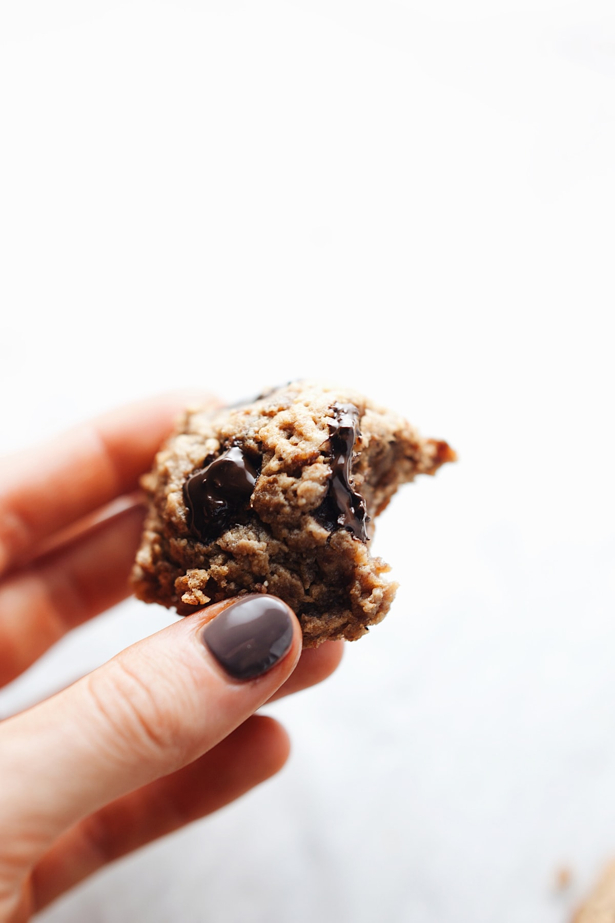 Fingers holding chocolate chip protein cookie with a bite out of it