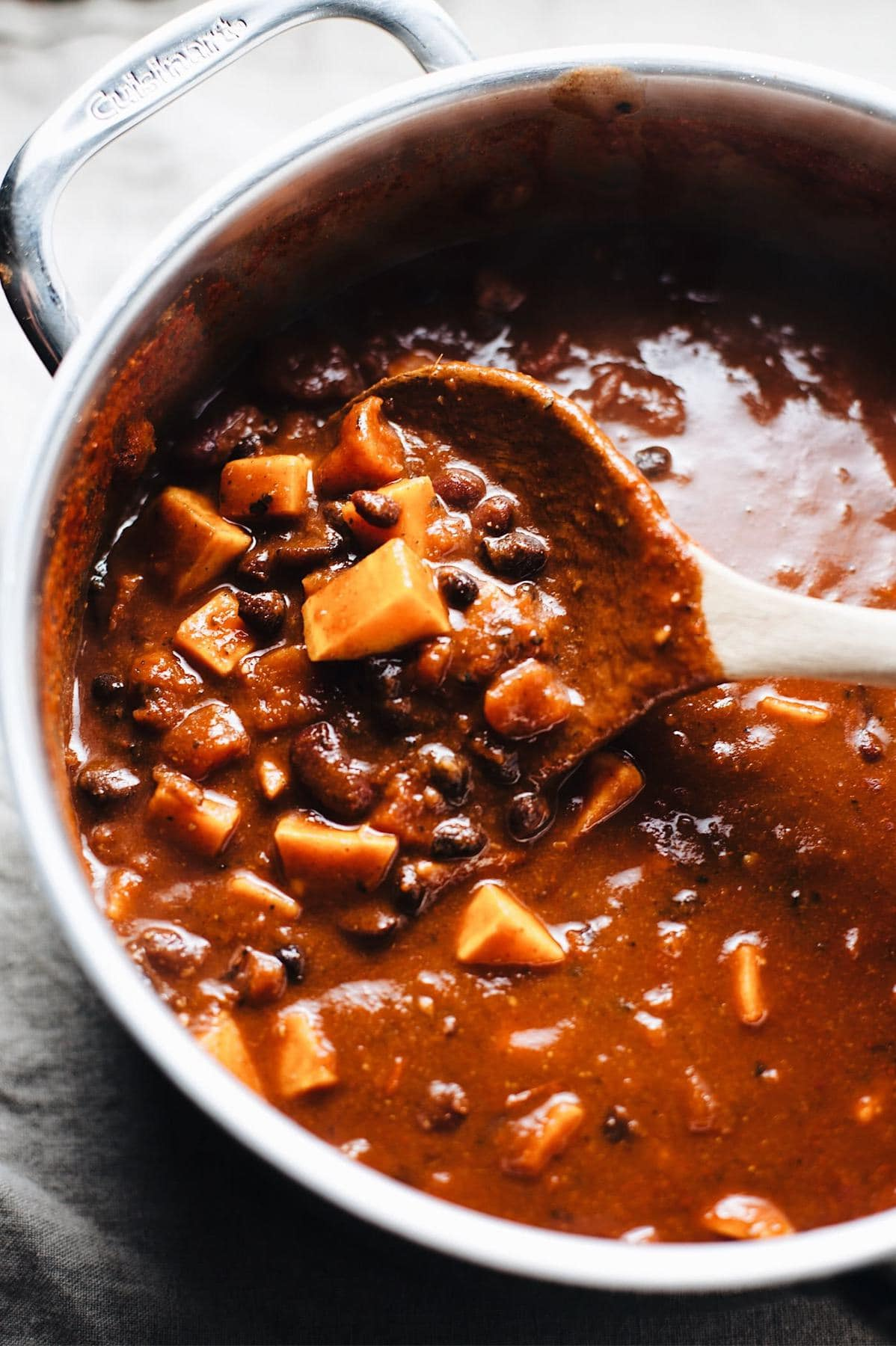A pot of sweet potato black bean chili with a spoon mixing it.