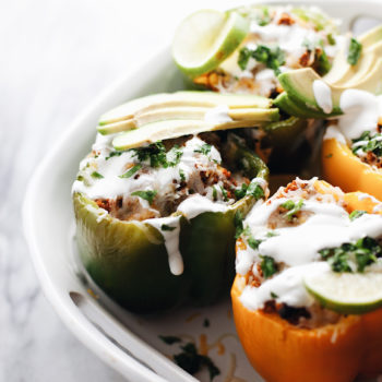 Stuffed peppers in a ceramic pot drizzled with sour cream