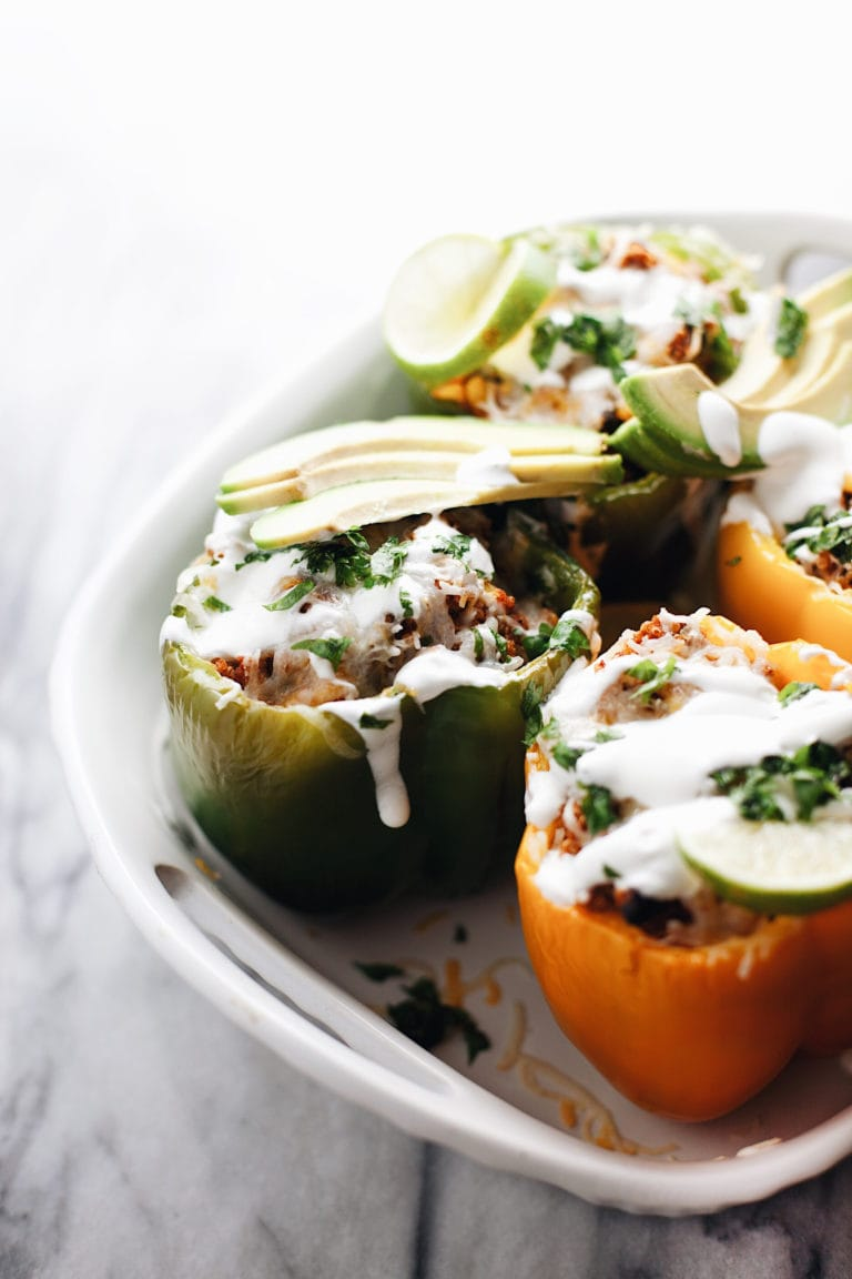 vegetarian stuffed bell peppers in a ceramic pot drizzled with sour cream