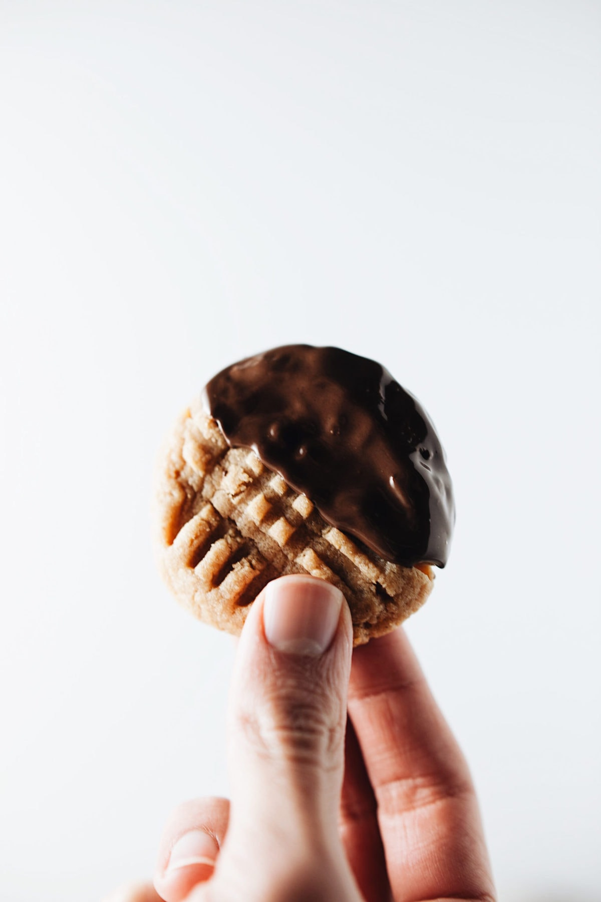 Hand holding up a chocolate-dipped peanut butter cookie with cross-hatch pattern