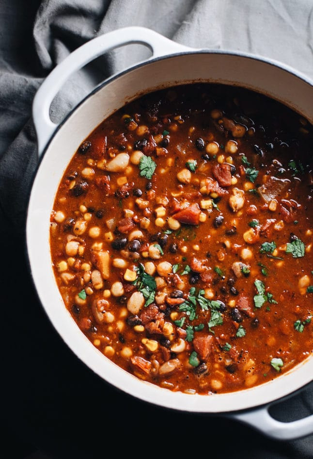 A white dutch oven with vegetarian bean chili in it.