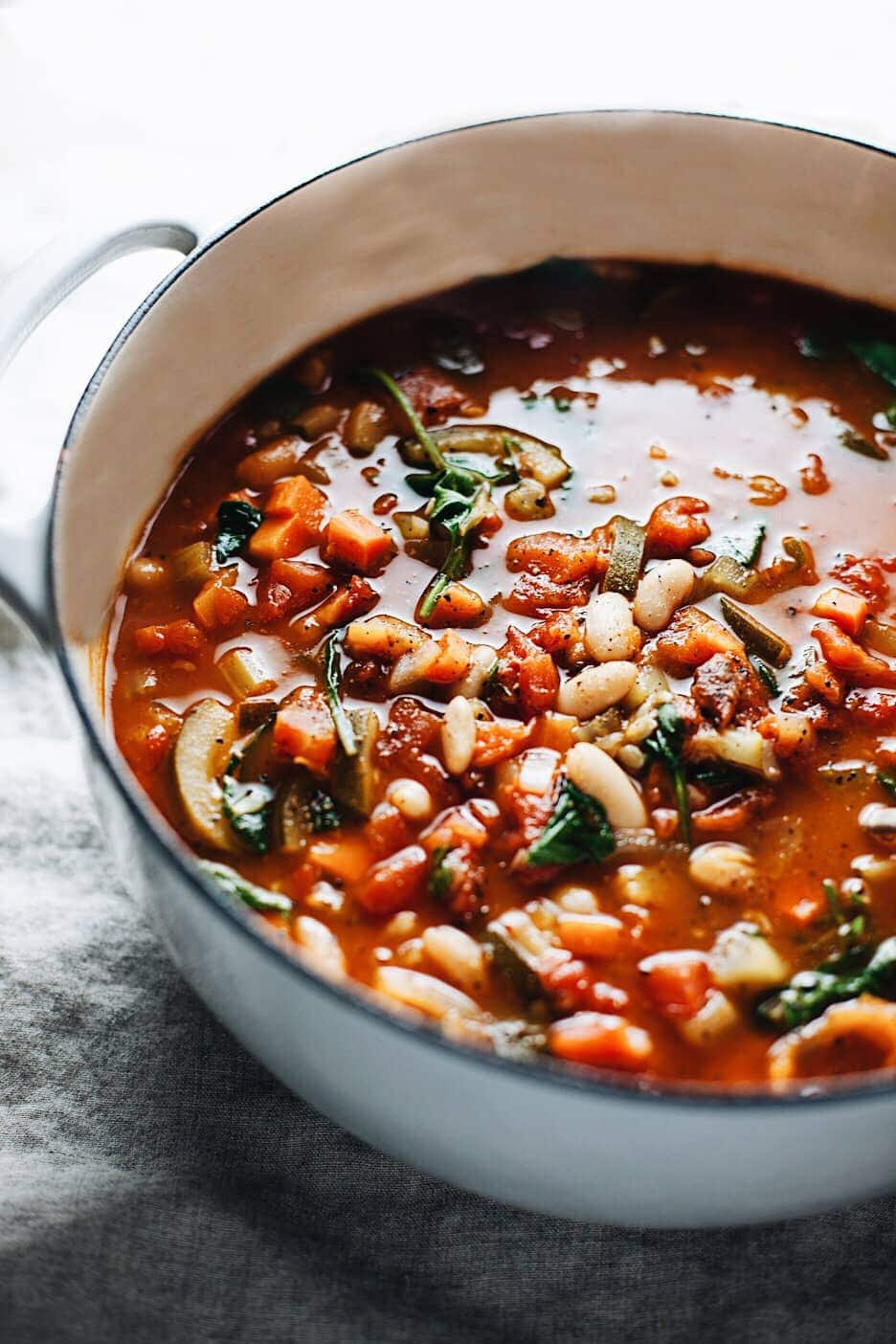 Vegetable bean soup in cast iron pot on dark gray background
