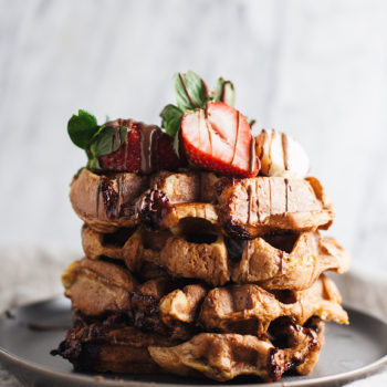 Pile of waffles with fruit on it.