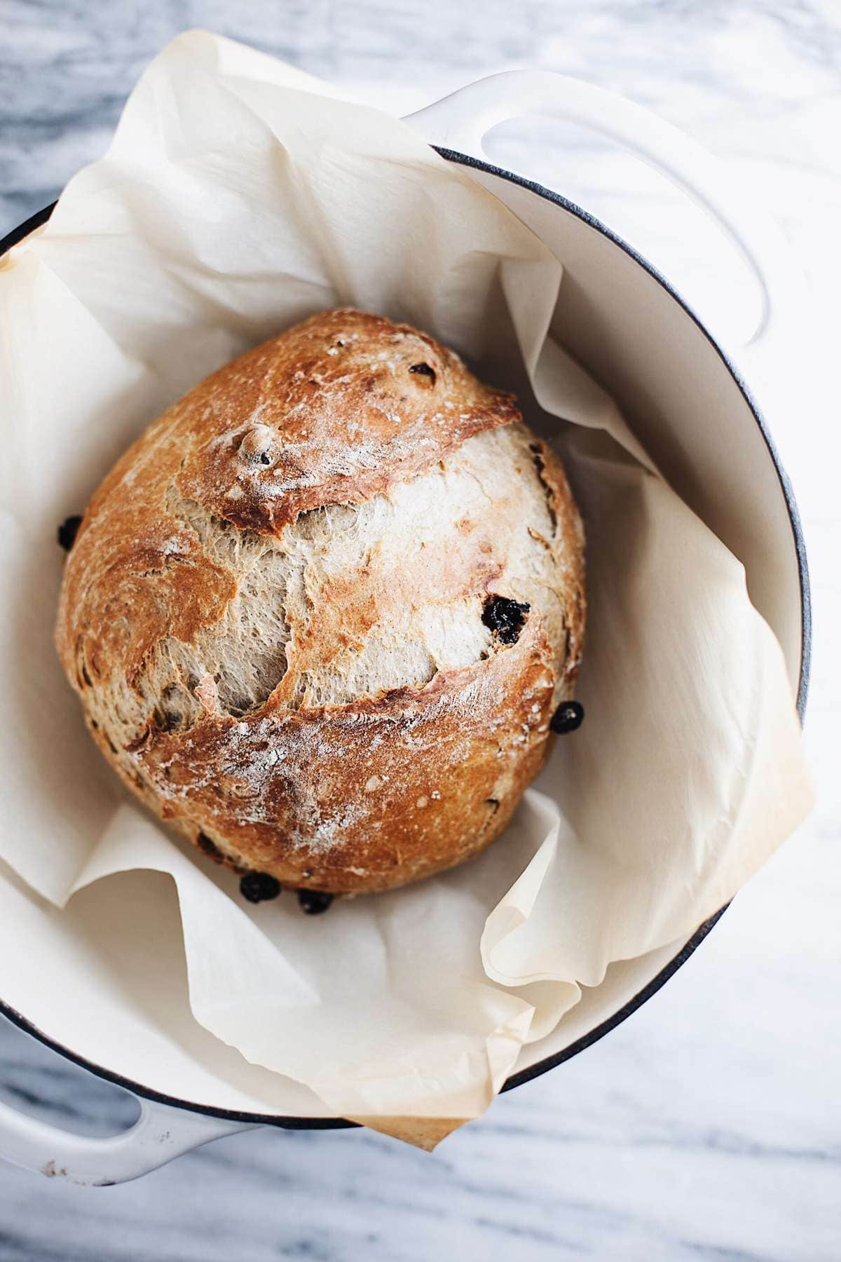 raisin bread recipe in a dutch oven with parchment papaer
