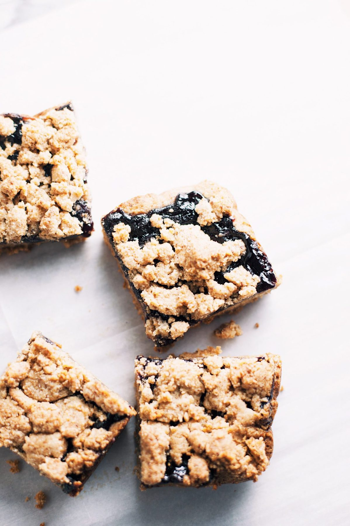 blueberry crumble bars on parchment paper