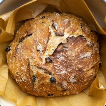 Cinnamon raisin artisan bread in a pot with brown parchment paper.