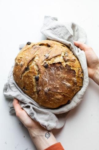 Hands holding a grey napkin with cinnamon raisin bread in it.