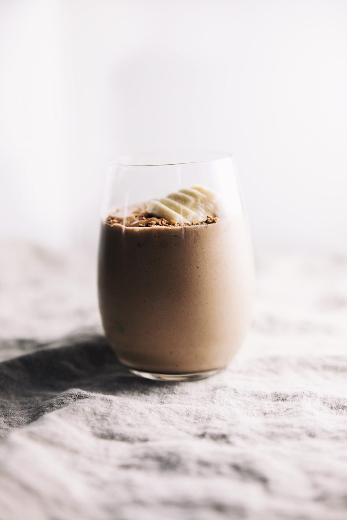 side angle of a glass of peanut butter banana protein shake with banana slices on top