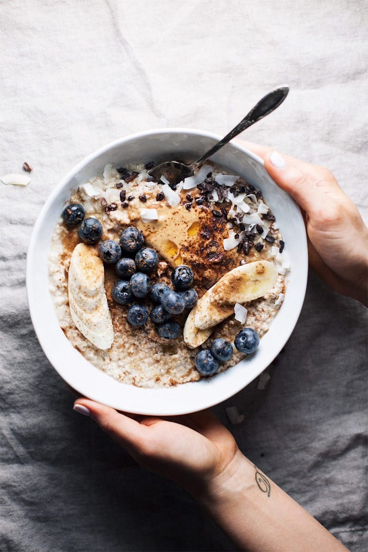 hands holding a white bowl of peanut butter oatmeal topped with blueberries, bananas, peanut butter