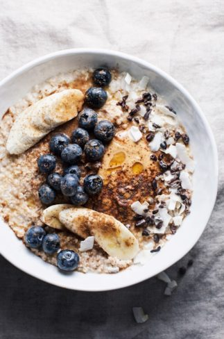 white bowl of peanut butter oatmeal topped with blueberries, bananas, peanut butter