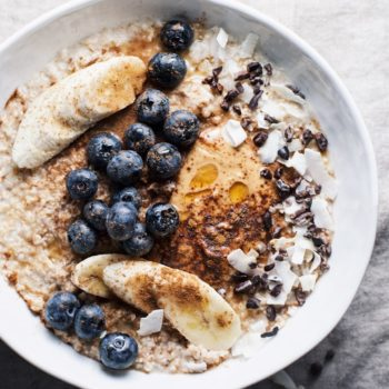 white bowl of oatmeal topped with bluberries, bananas, peanut butter