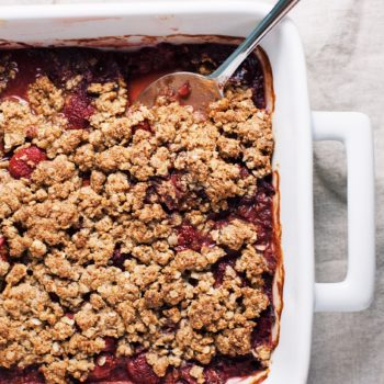 Close up of berry rhubarb crisp with spoon in it