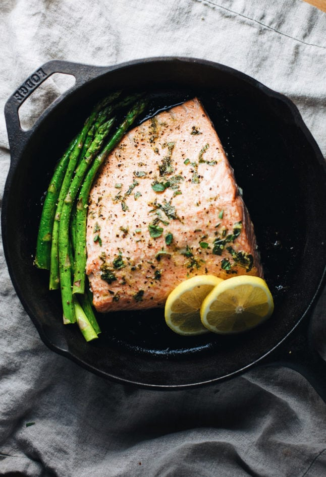 salmon in a cast iron pan with asparagus and lemon