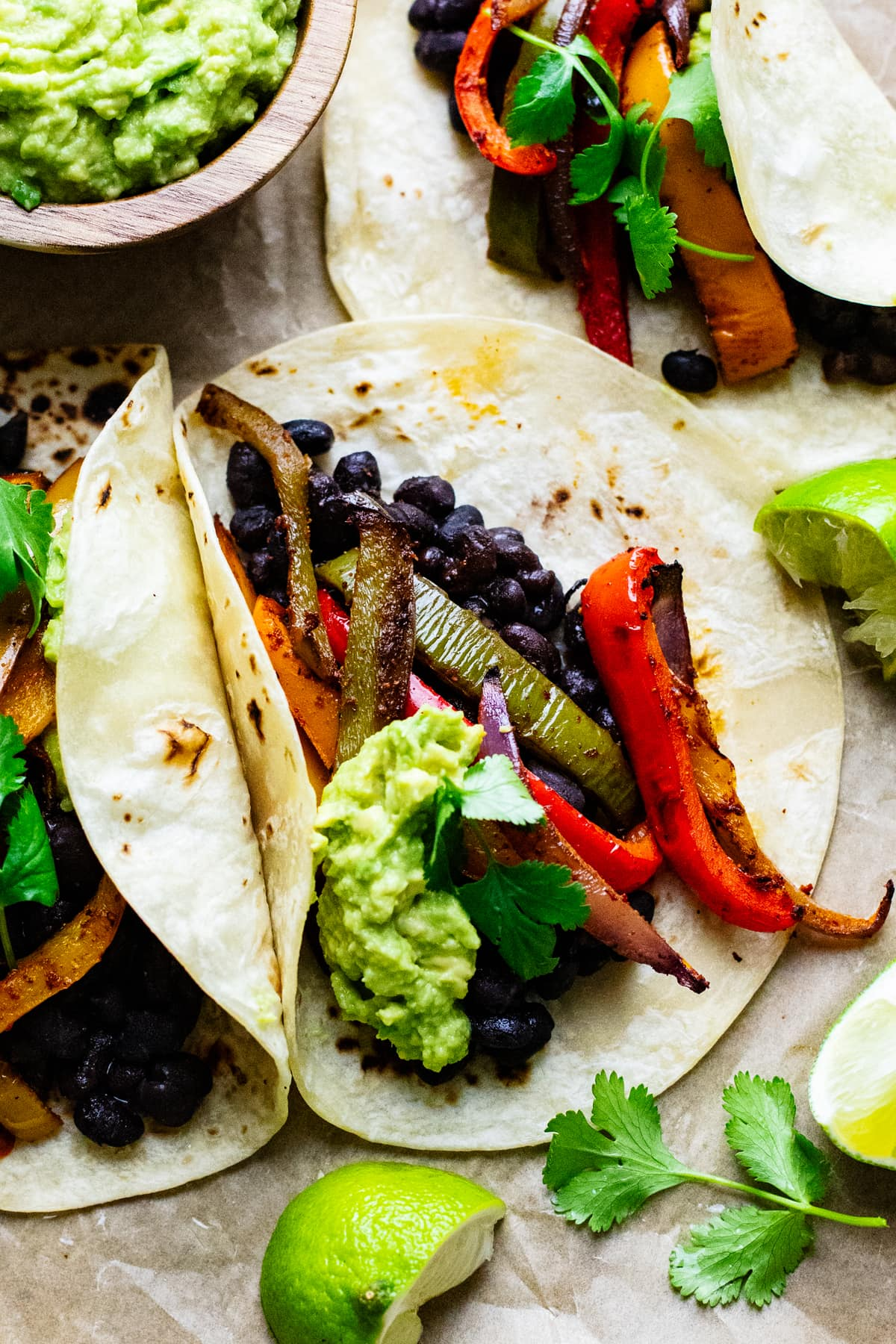 vegetarian fajitas arranged on parchment paper with lime slices and guacamole arranged around them.