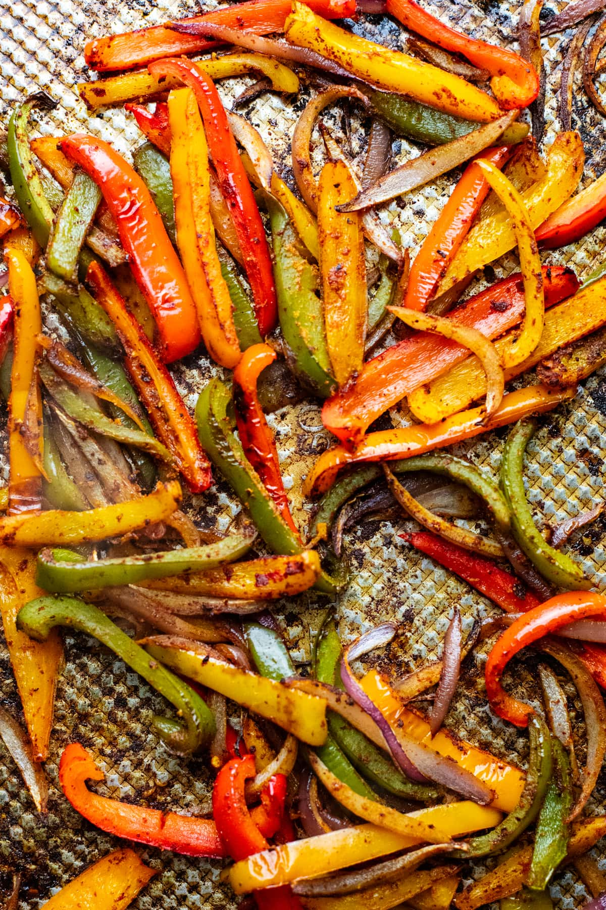 different colored roasted peppers and onions on baking sheet.