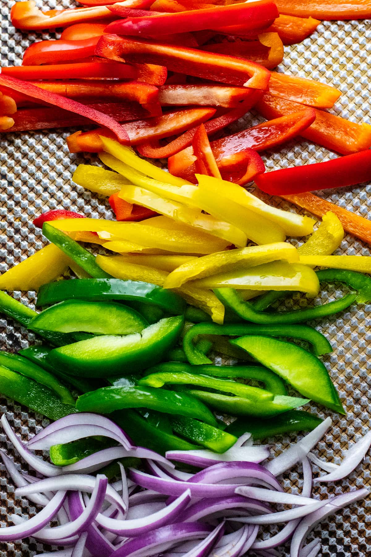 different colored bell pepper slices and red onion on sheet pan.