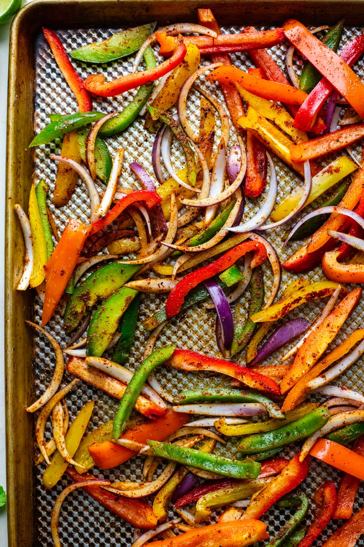 different colored sliced bell peppers and red onion on sheet pan.
