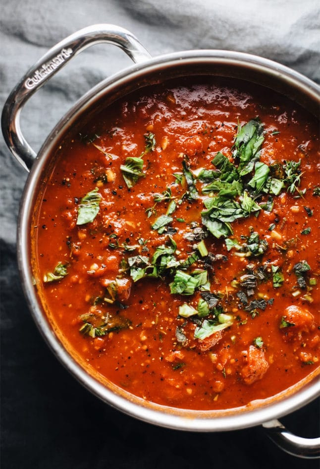 a pot of san marzano tomato sauce with fresh herbs
