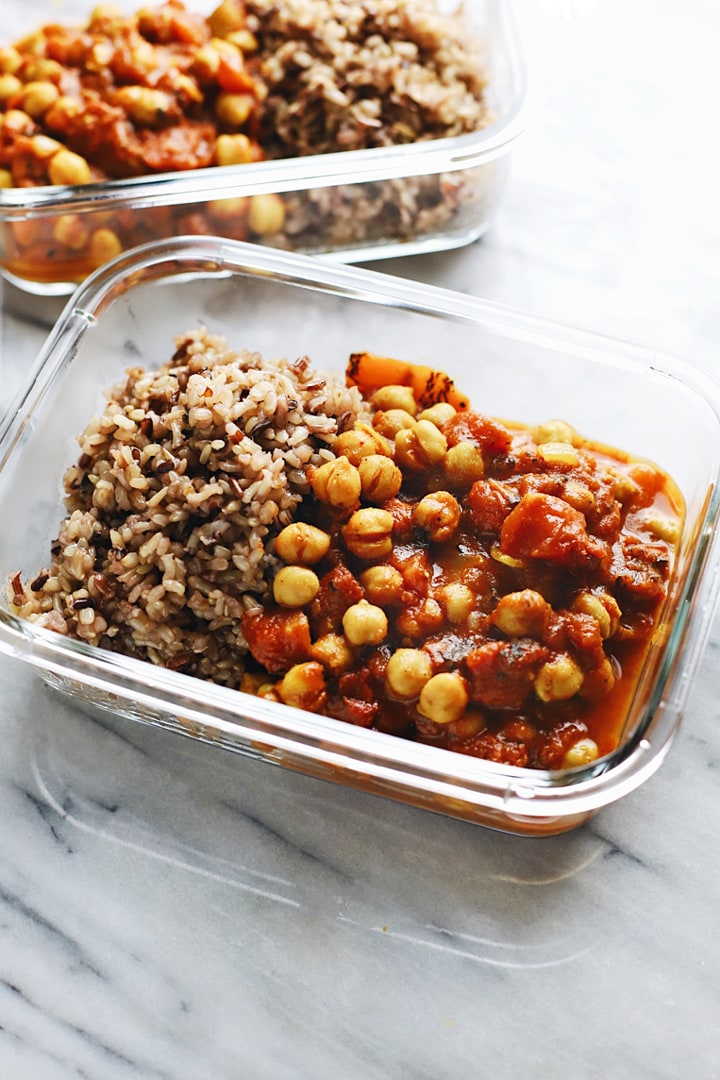 Moroccan chickpea stew in a glass storage bowl with rice.