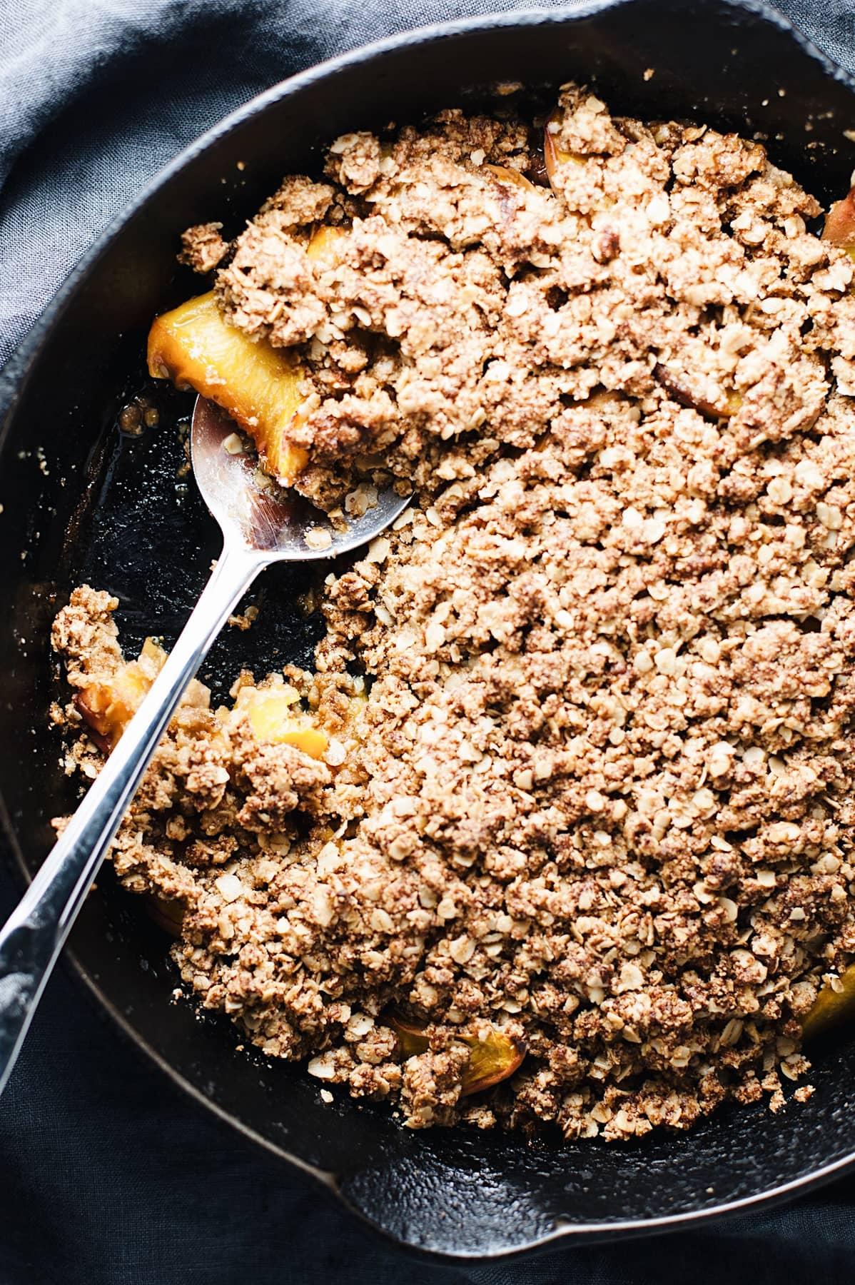 a cast iron skillet with gluten free peach crisp and a spoon in it