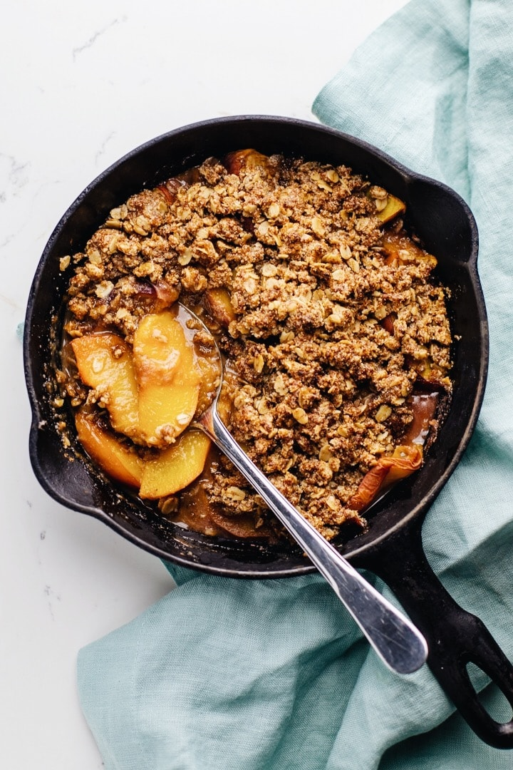 gluten free peach crisp in a cast iron pan with a serving spoon and a light blue napkin