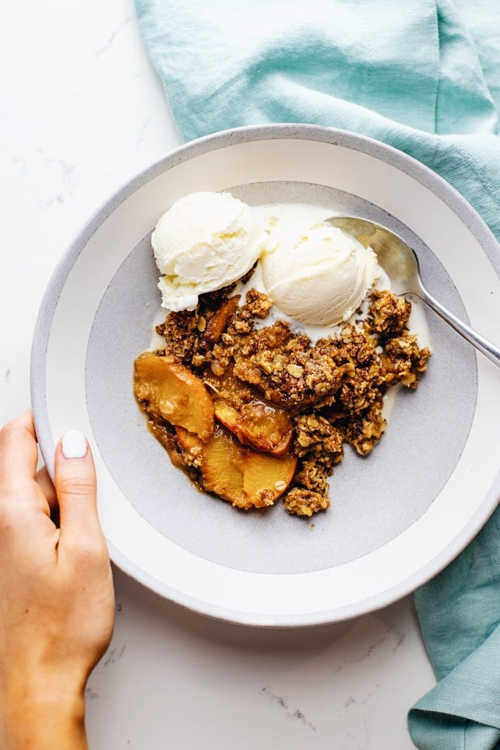 A hand holding a white bowl of gluten free peach crisp and vanilla ice cream over a light blue napkin.