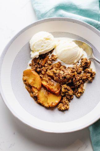 a white bowl of gluten free peach crisp and vanilla ice cream over a light blue napkin.