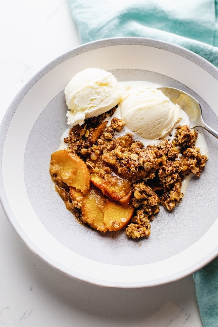 a white bowl of gluten free peach crisp and vanilla ice cream over a light blue napkin.